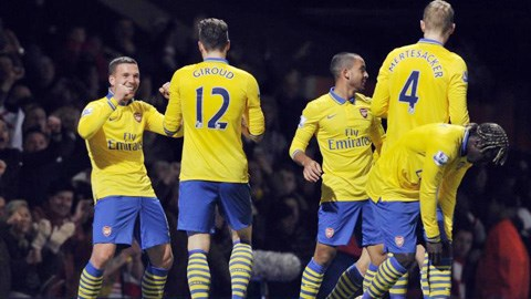 Lukas Podolski (trái) ghi bàn ấn định chiến thắng cho Arsenal