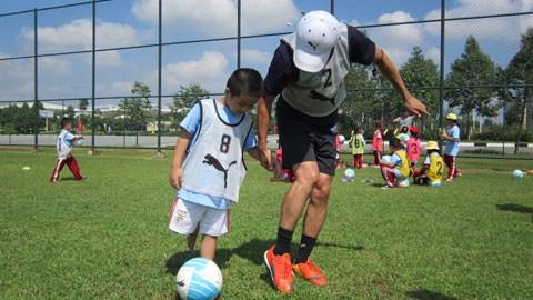 HLV đến từ Kawasaki Frontale đang hướng dẫn 1 em tham gia chương trình chơi bóng