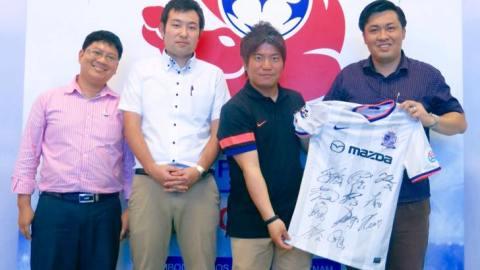 Đại diện BLĐ Sanfrecce Hiroshima tặng áo đấu của CLB cho TGĐ B.BD - ông Cao Văn Chóng (ngoài cùng bên phải)