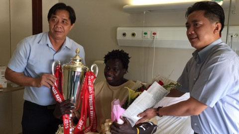 Đại diện lãnh đạo đội B.Bình Dương mang cúp vô địch vào thăm Abass. Ảnh: Minh Châu